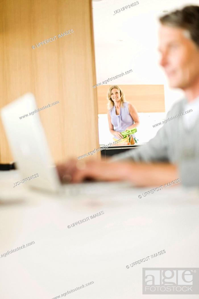 Stock Photo: Woman in kitchen watching husband using laptop.