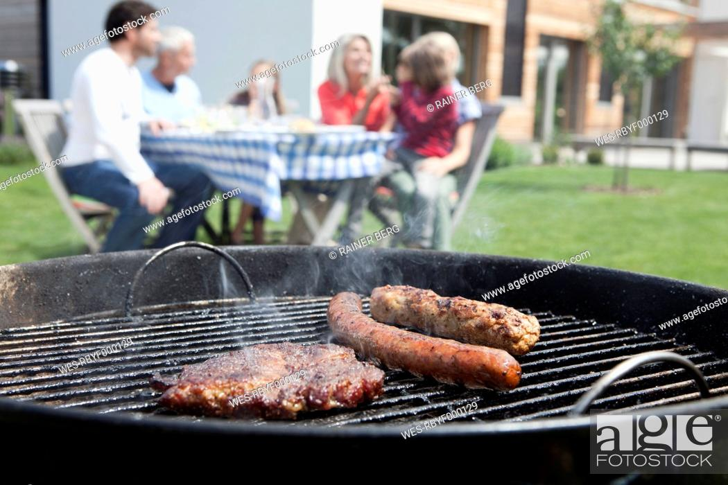 Stock Photo: Germany, Bavaria, Nuremberg, Close up of barbecue, family sitting in background.