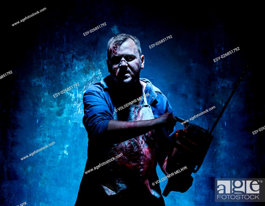 Stock Photo: Bloody Halloween theme: crazy killer as bloody butcher with electric saw on dark blue background.