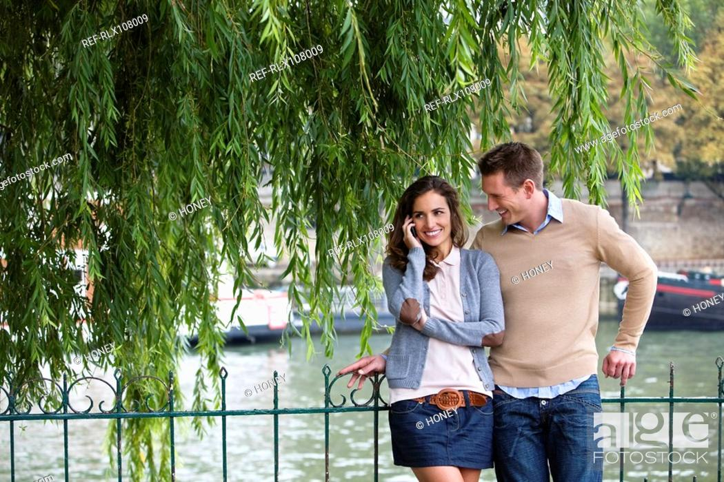 Stock Photo: Young couple by river Seine, woman using mobile phone, Paris, France.