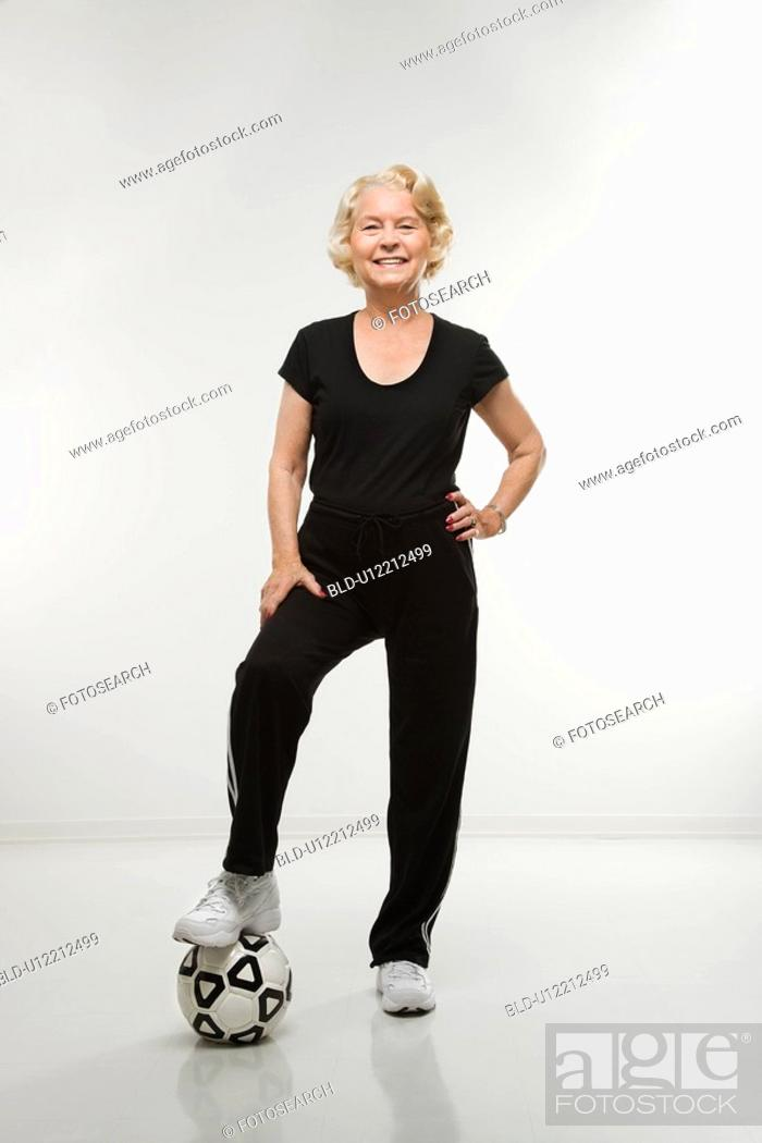 Stock Photo: Woman standing with foot on soccer ball.