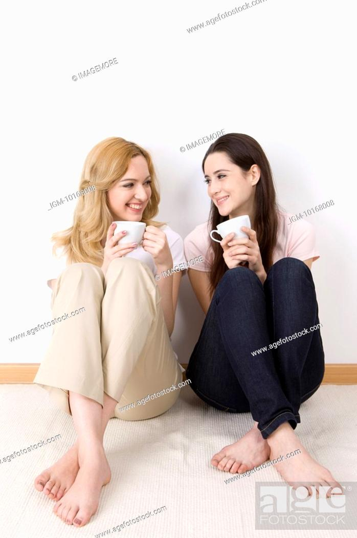 Stock Photo: Tow women sitting together drinking coffee.