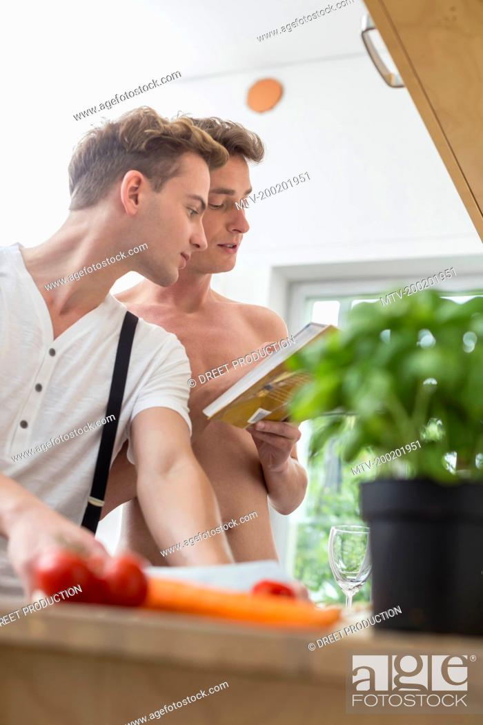 Stock Photo: Homosexual couple cooking food in kitchen.
