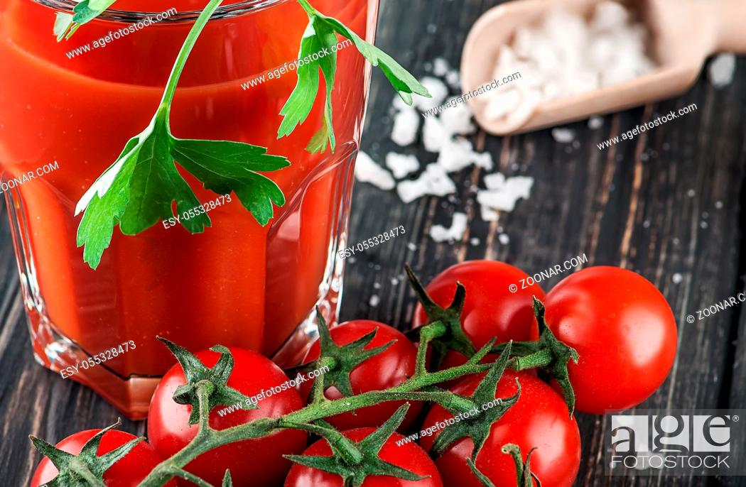 Stock Photo: Closeup of tomato juice and cherry tomatoes. Blurred background.