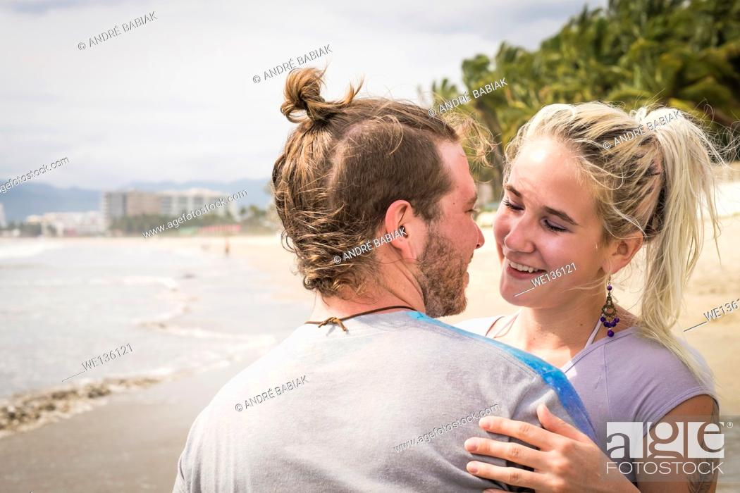 Stock Photo: Close up of young people, man and woman, hugging and about to kiss each other at a beach. Riviera Nayarit, Pacific Coast, Mexico.