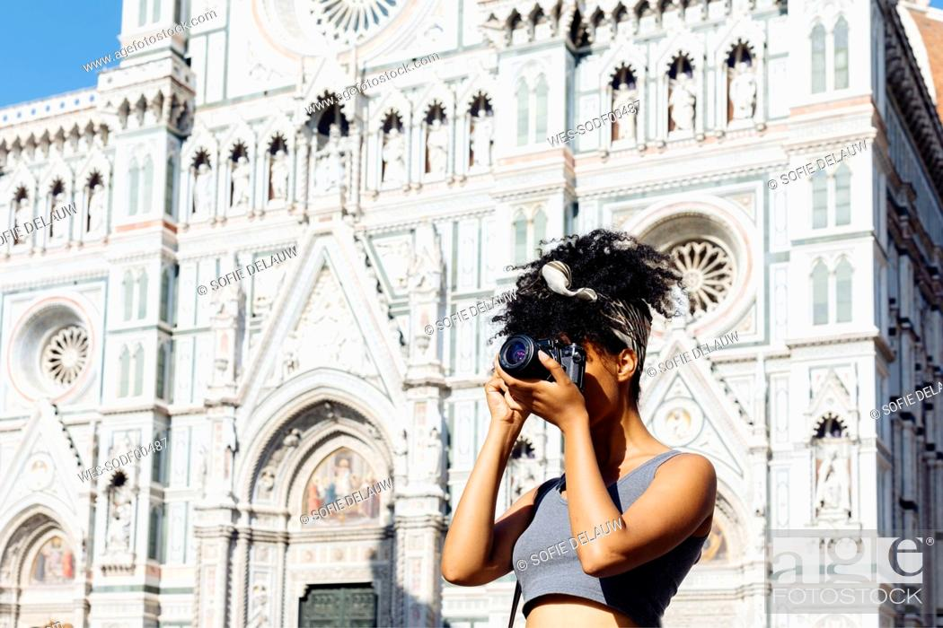 Stock Photo: Young woman taking photo with camera in front of cathedral, Florence, Italy.