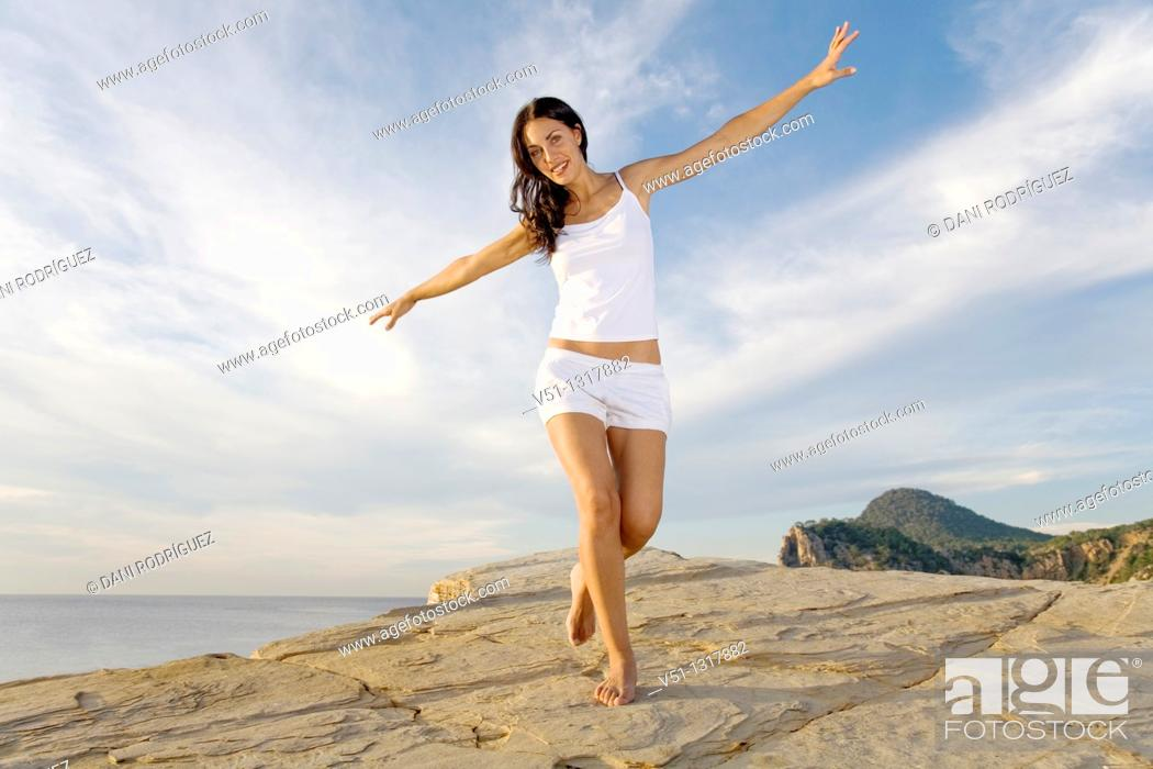 Stock Photo: Brunette palyful woman in a cliff in Ibiza, Balearic Islands.