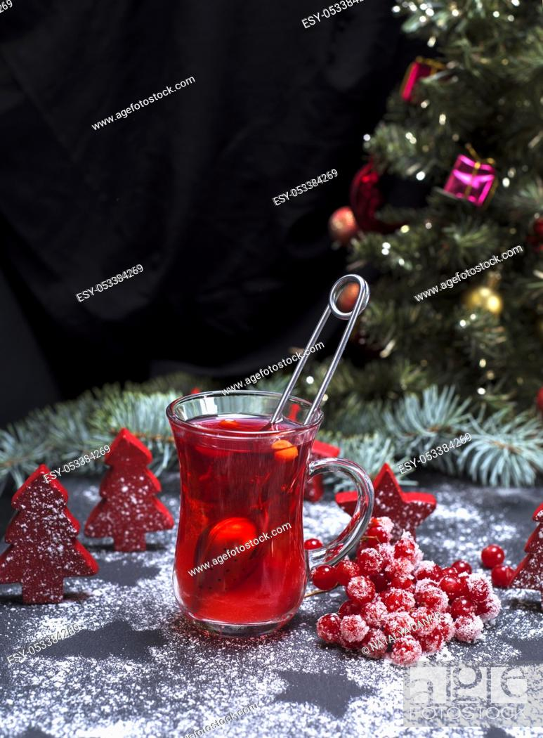 Stock Photo: red viburnum tea in a glass on a black background, behind Christmas decorations and a Christmas tree.