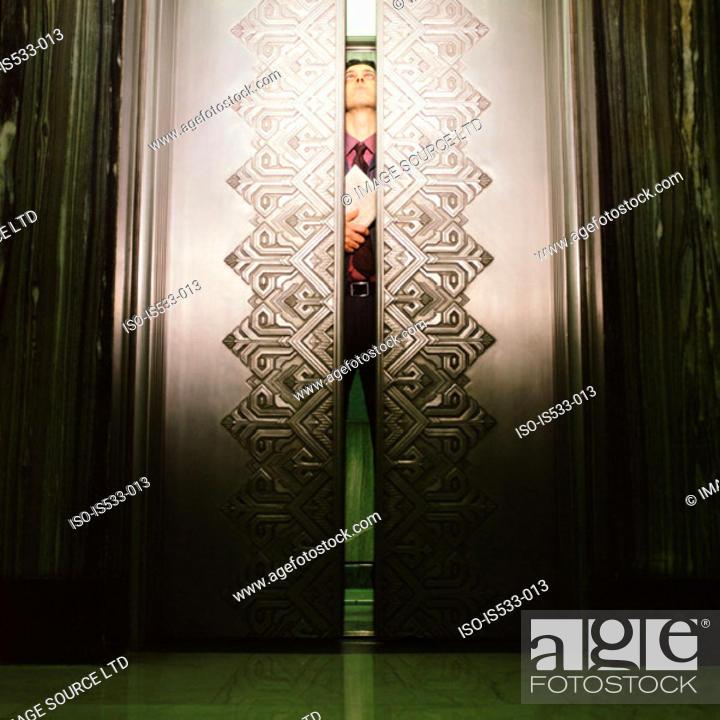 Stock Photo: Man peering through elevator doors.