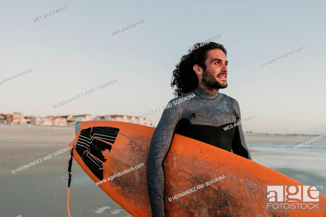 Photo de stock: Portrait of surfer on the beach at sunset, Costa Nova, Portugal.