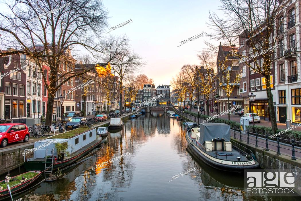 "Photo de stock: A boat reading """"Amsterdam"""" is docked to a canal with many other boats in Amsterdam, Netherlands."