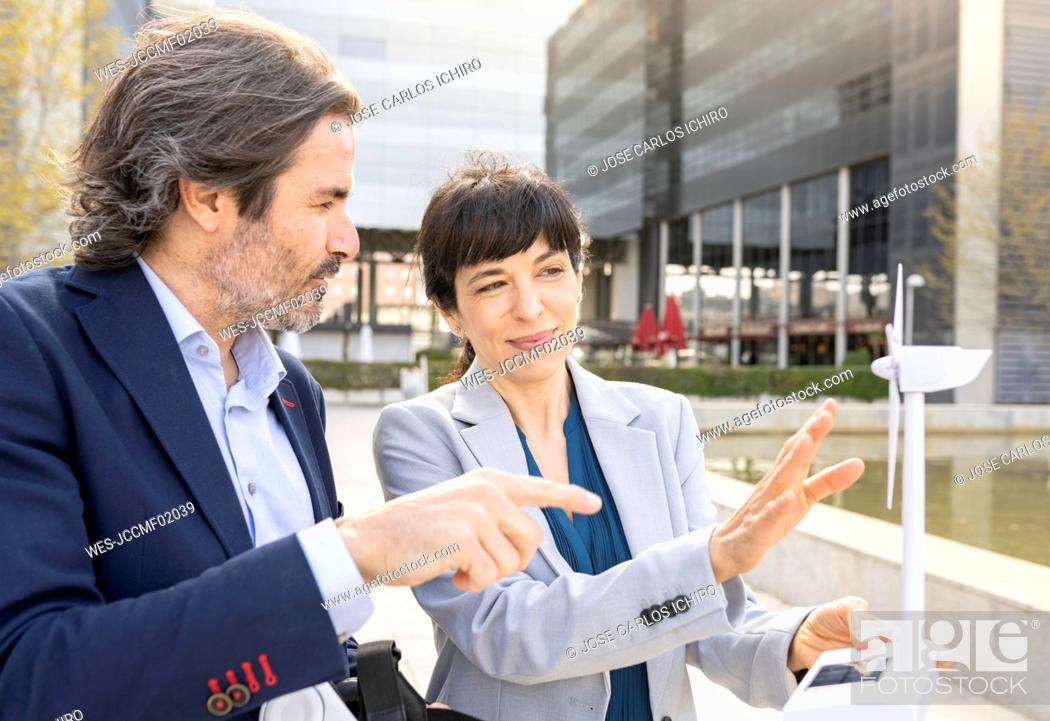 Stock Photo: Mature female engineer explaining wind turbine model with male colleague in park.
