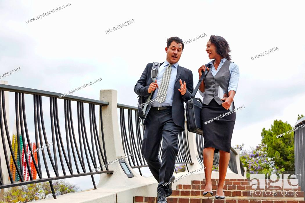 Imagen: Low angle view of business people descending stairway carrying briefcases and digital tablet.
