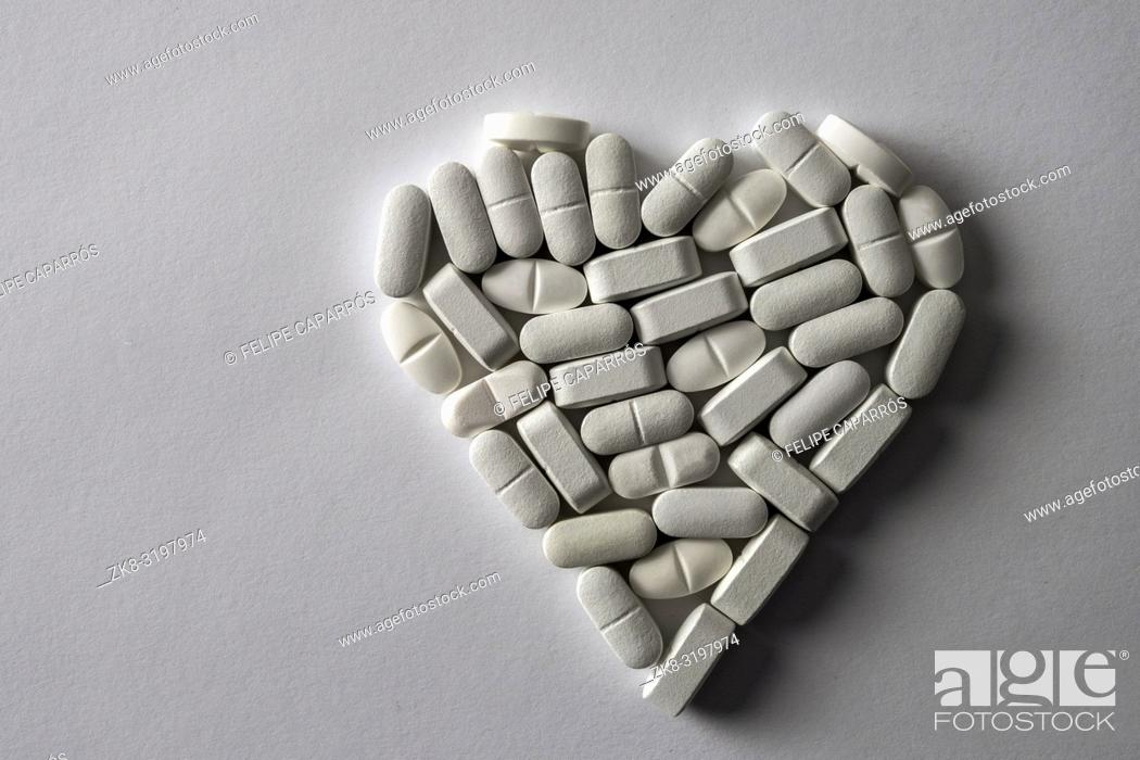 Stock Photo: White pills in the shape of heart isolated on white fund, conceptual image.