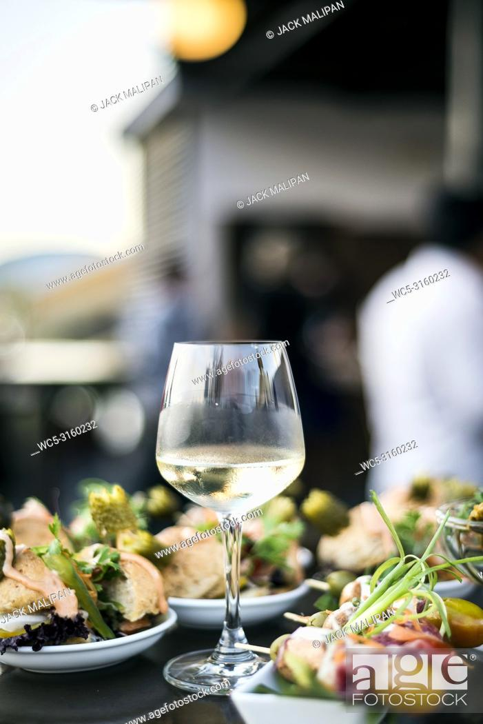 Imagen: glass of white wine with gourmet food tapa snacks in outdoors bar at sunset.