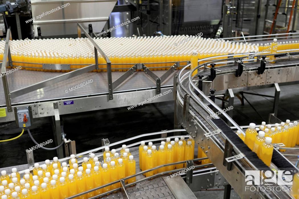 Stock Photo: Packed bottles moving on conveyor belt.