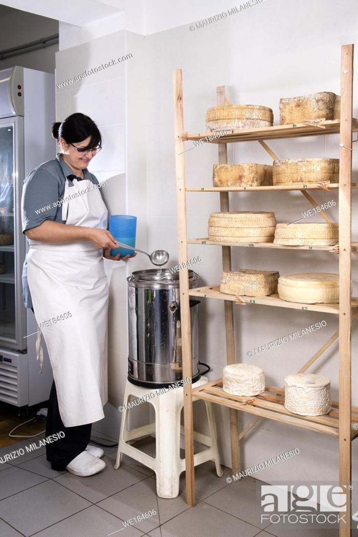 Stock Photo: Cheesemaker pours the rennet with a ladle and a jug.