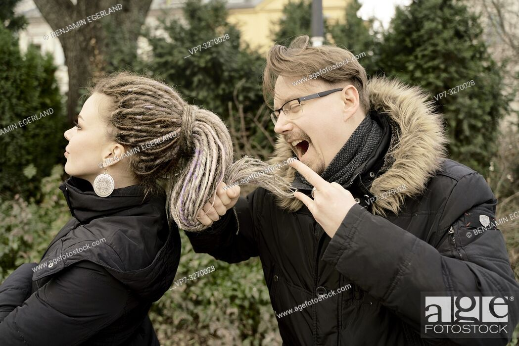 Stock Photo: man using hair of woman as microphone, screaming loud his opinion, multiracial couple, in Cottbus, Brandenburg, Germany.