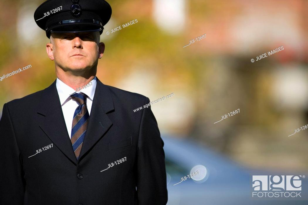 Stock Photo: Chauffeur by car, portrait, low angle view lens flare.