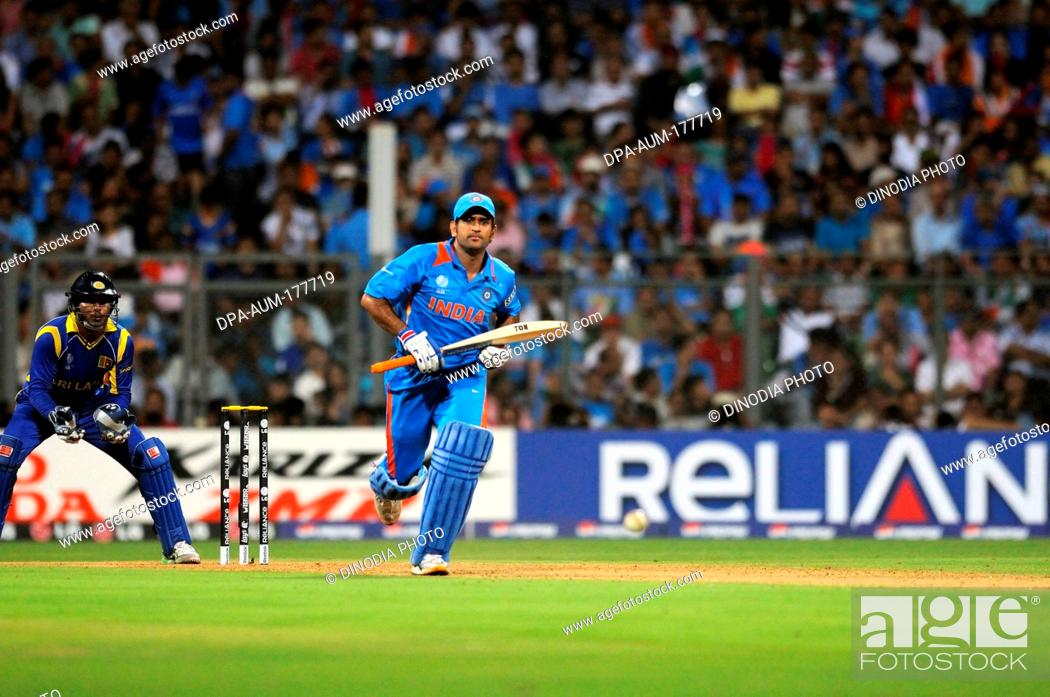Stock Photo: Indian batsman M S Dhoni plays his shot while Sri Lankan captain, wicketkeeper Kumar Sangakkara looks on during the ICC Cricket World Cup final between India.