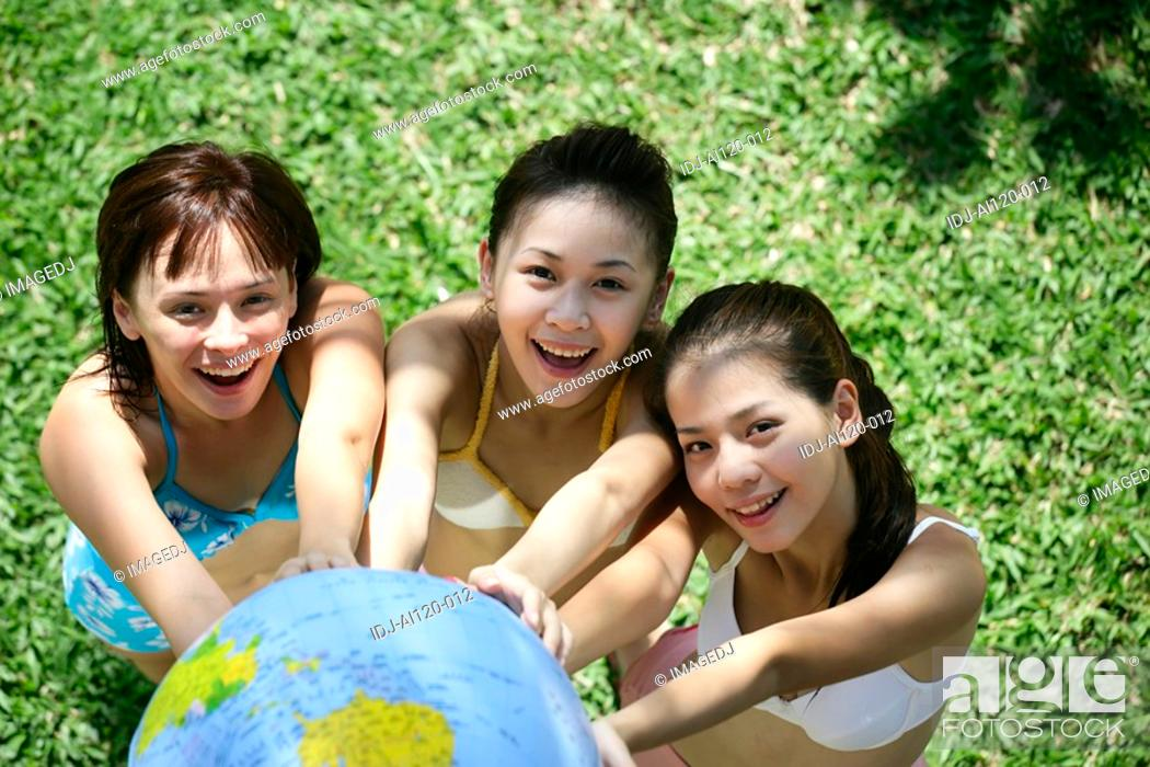 Stock Photo: Portrait of three teenage girls with globe in garden.