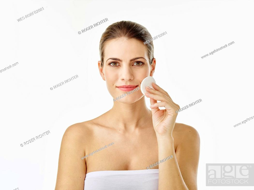 Stock Photo: Portrait of smiling woman cleaning face with cotton pad.