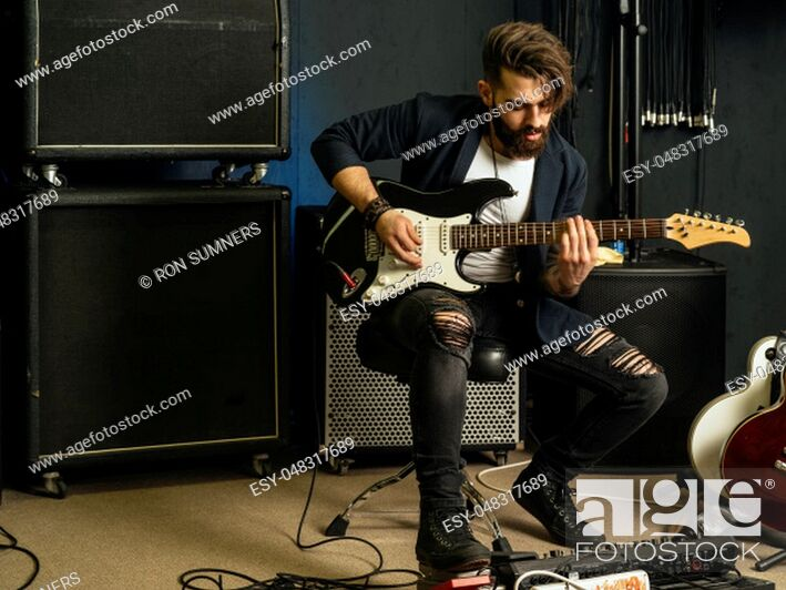 Stock Photo: Photo of a man with beard sitting and playing his electric guitar in a recording studio.