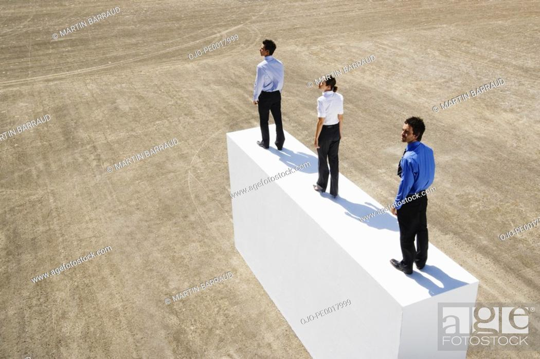 Stock Photo: Three businesspeople standing on wall outdoors.