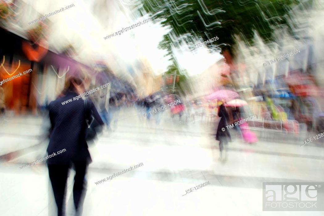 Stock Photo: Shoppers walking along pedestrian precinct, motion blurred.