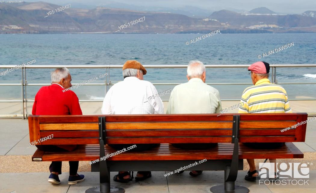 Stock Photo: Four elderly men sitting on bench at coast In Spain.