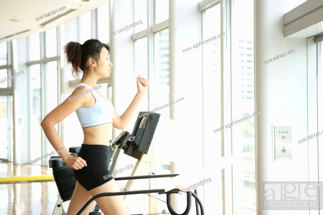 Stock Photo: A young woman jogs on a walker as she exercises in a well equipped gym.