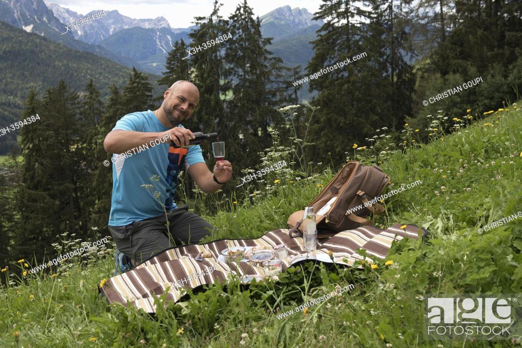 Stock Photo: homme servant le vin au cours d'un pique-nique prepare par le chef etoile Chris Oberhammer du Restaurant Tilia a Dobbiaco.