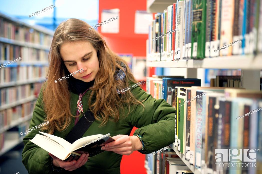 Stock Photo: Tilburg, Netherlands. Young brunette reading a book in the public library, standing between the bookshelves with books.