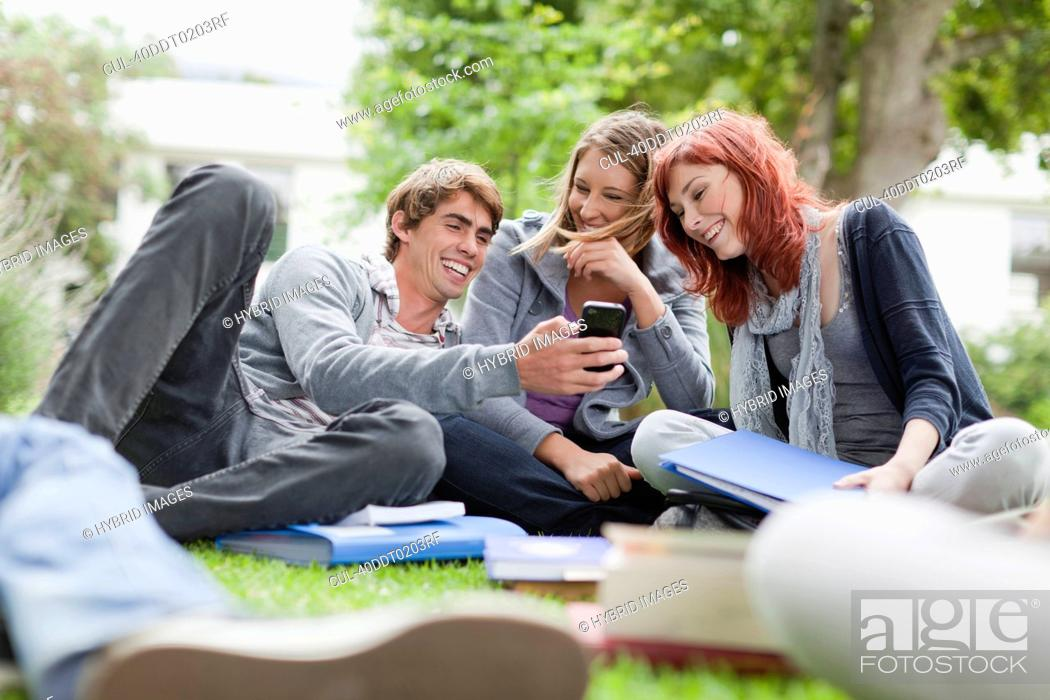 Stock Photo: Students using cell phone on grass.