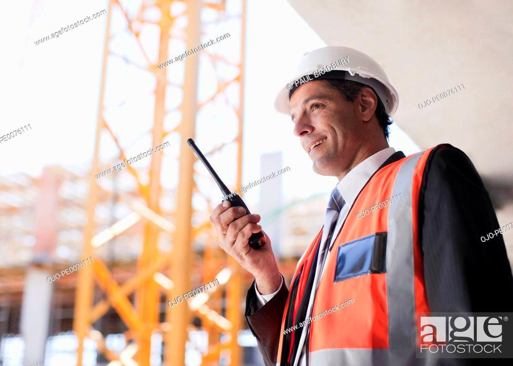 Stock Photo: Construction worker talking on walkie talkie on construction site.