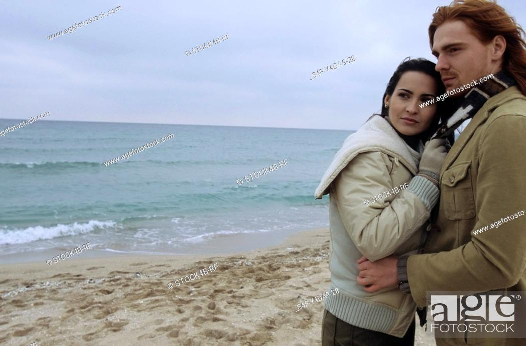 Stock Photo: Young auburn-haired Man holding a brownhaired young Woman in his Arms - Love - Togetherness - Beach.