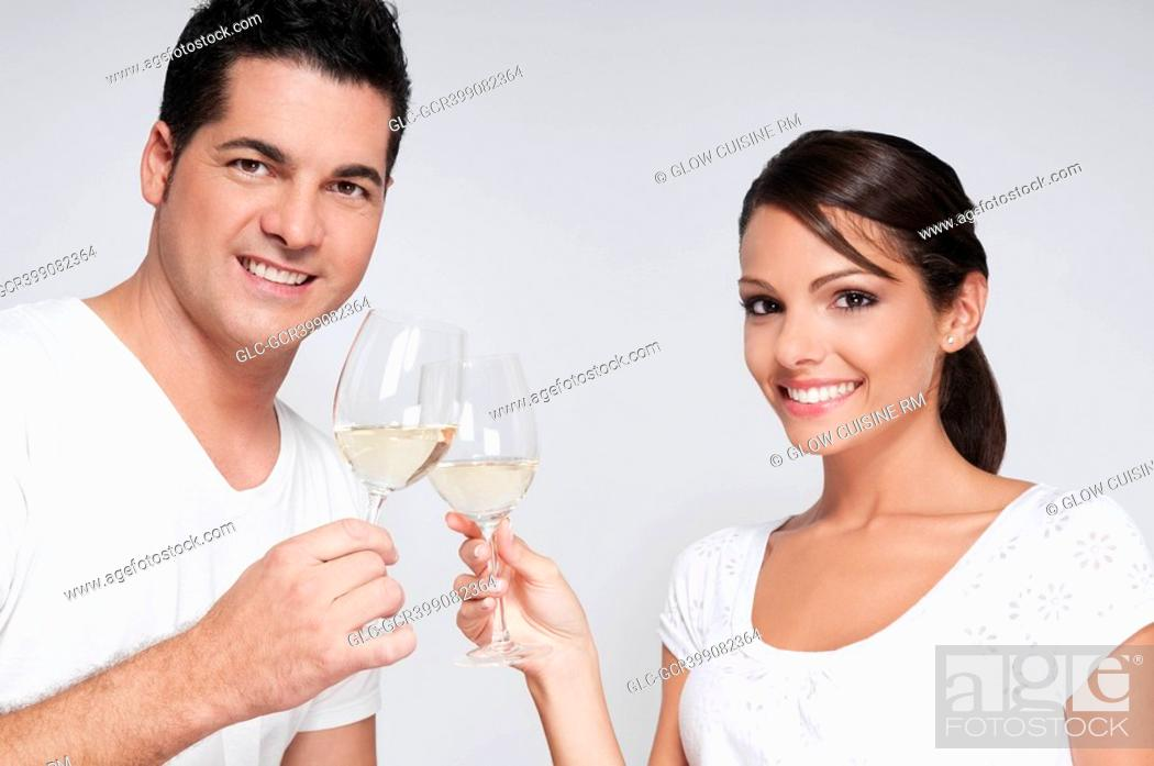 Stock Photo: Couple toasting with white wine glasses.