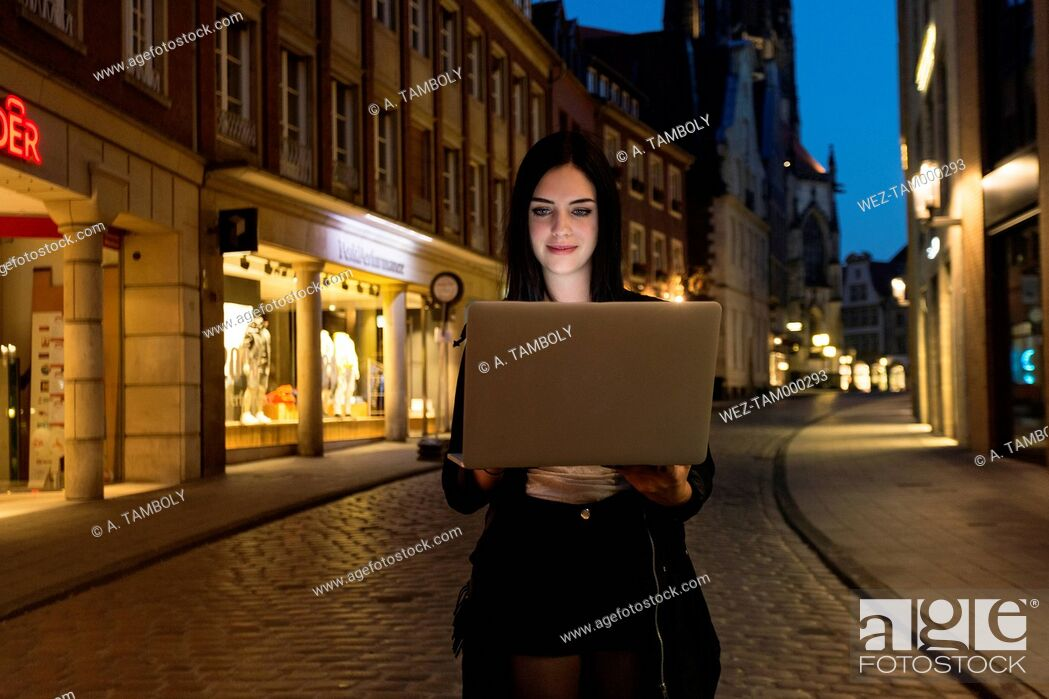 Stock Photo: Germany, Muenster, portrait of young woman using laptop in the city at evening.