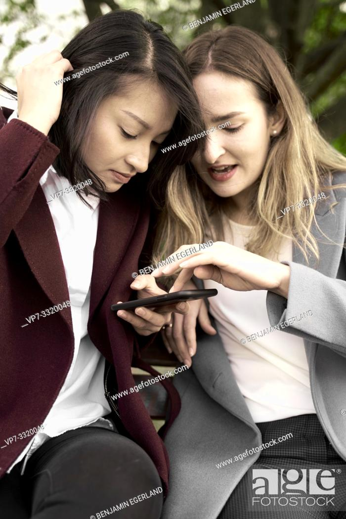 Stock Photo: two women checking together news on smartphone, in Frankfurt am Main, Germany.