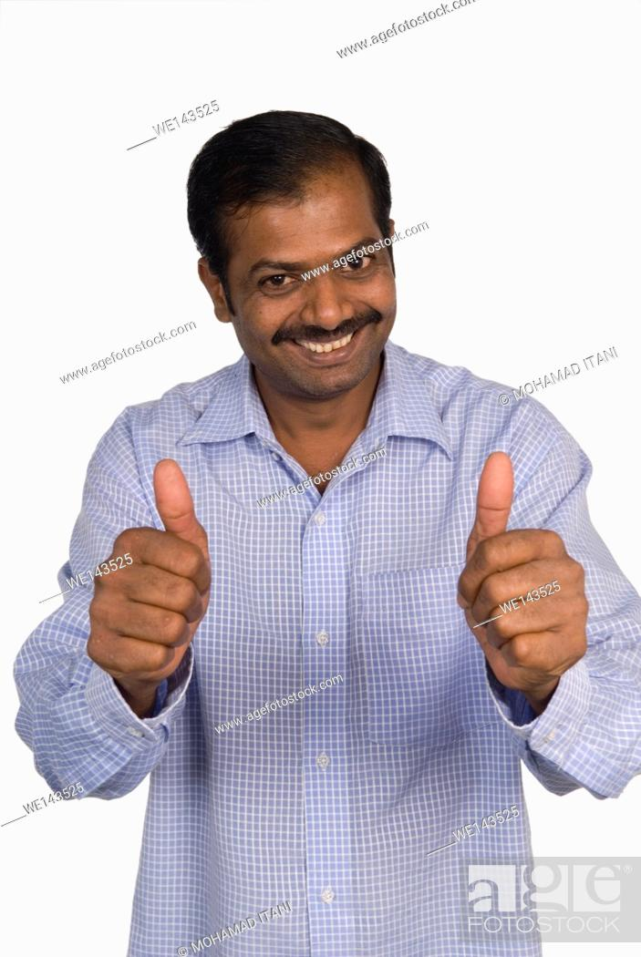 Stock Photo: Mature Indian man thumbs up.
