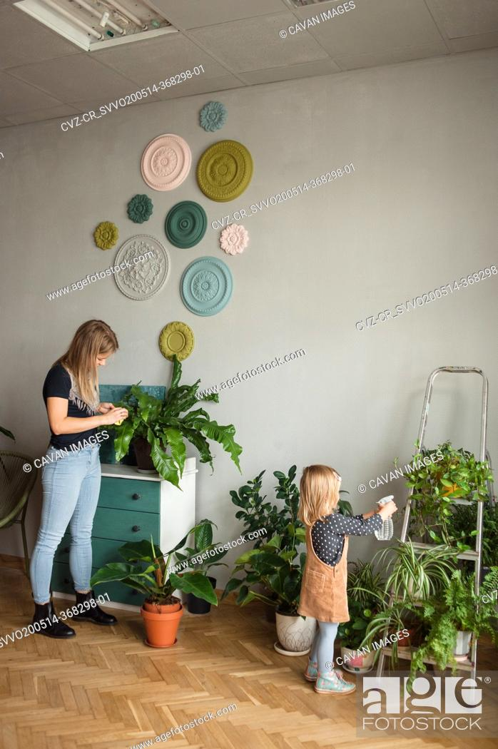 Stock Photo: Woman and child care about green plants at cozy modern apartment.