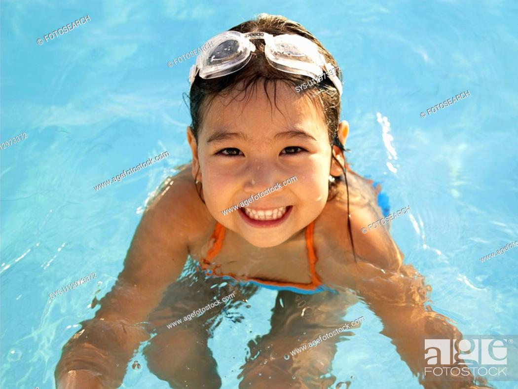Stock Photo: Young girl in swimming pool portrait, high angle view.