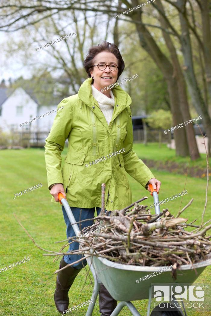 Stock Photo: Woman pushing a wheelbarrow full of branches.