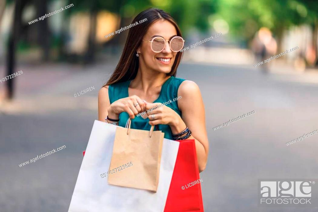 Stock Photo: Portrait of young happy smiling woman with shopping bags enjoying in shopping. Positive emotions and Shopping day concept.