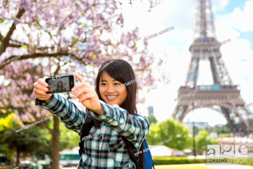 Stock Photo: View of a Young attractive asian tourist in Paris taking selfie.