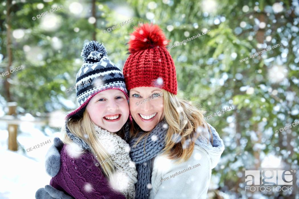 Photo de stock: Mother and daughter hugging in snow.