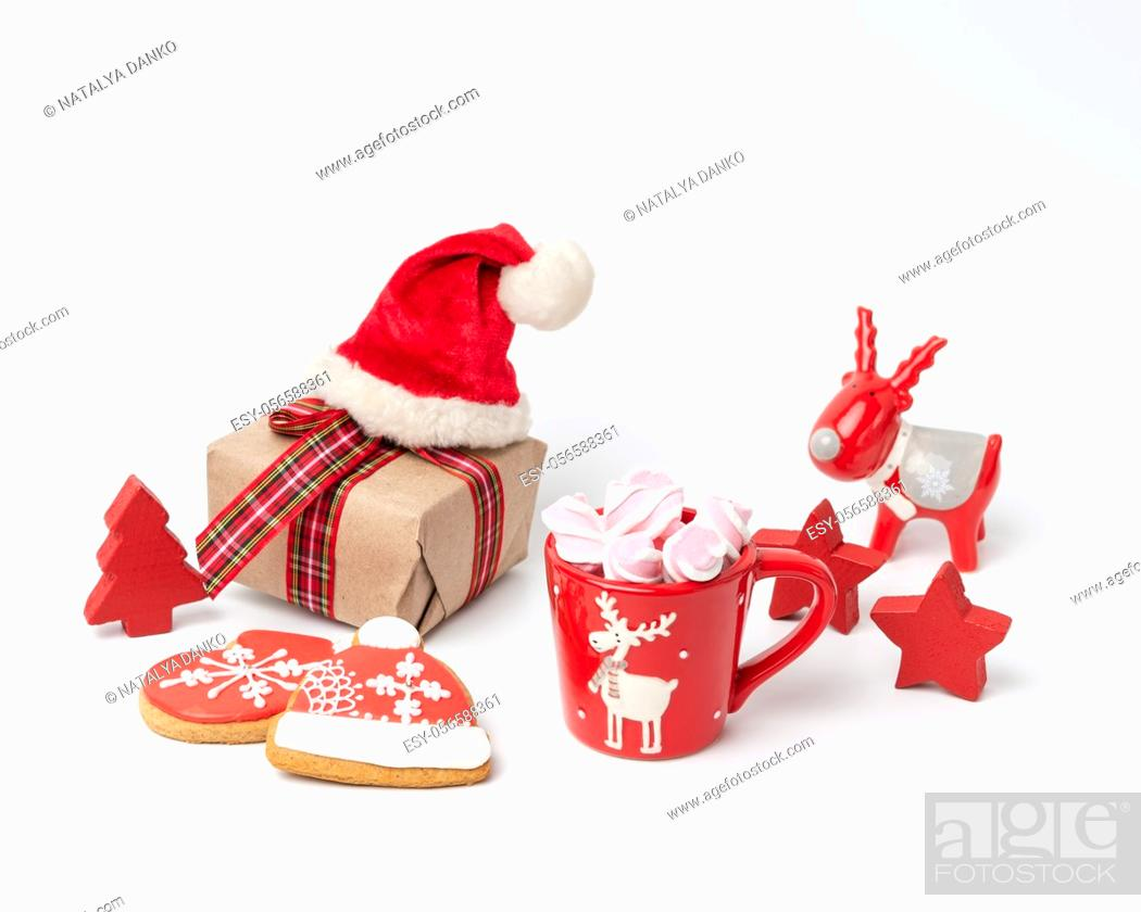 Stock Photo: red ceramic cup with drink and marshmallows, near baked christmas gingerbread, white background.