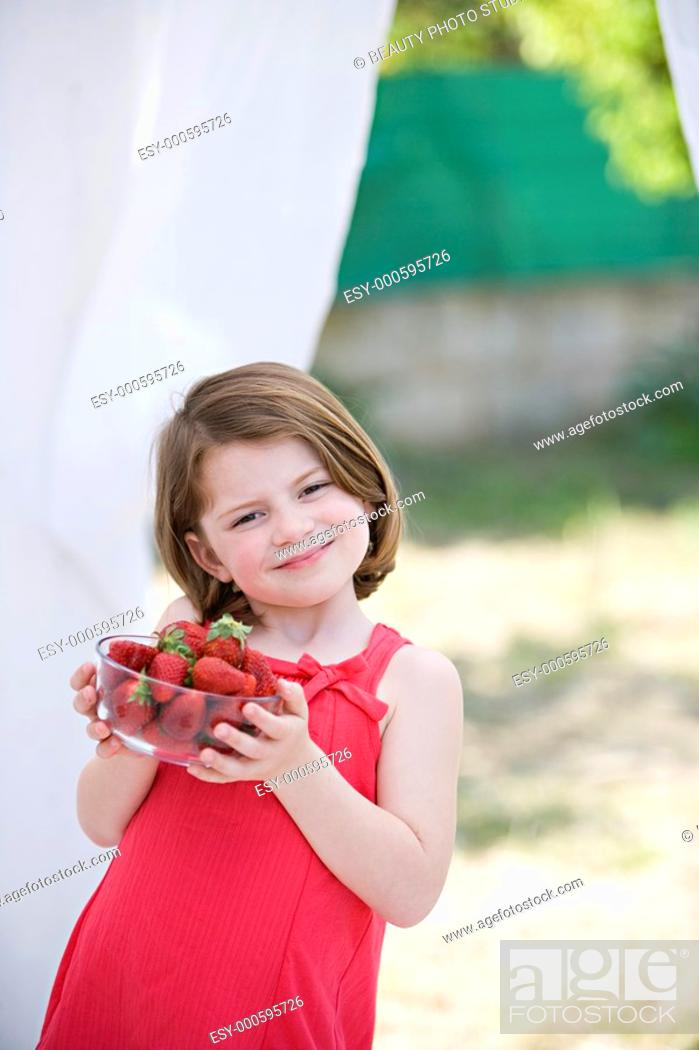 Imagen: Caucasian girl holding a bowl with nice strawberries.