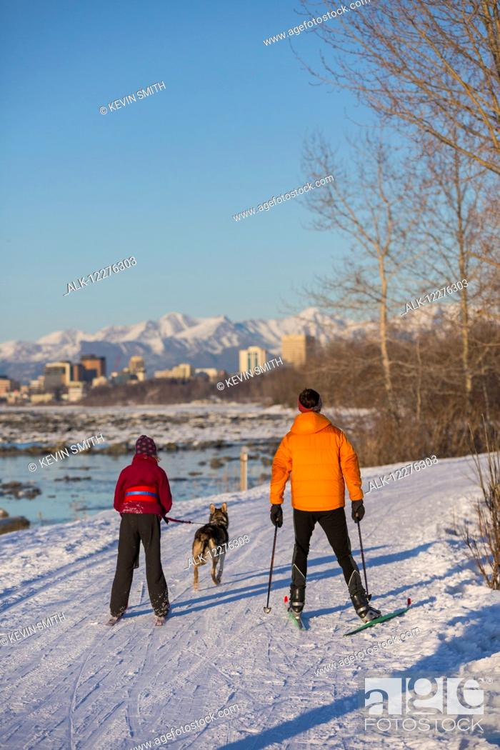 Imagen: People cross country ski and skijor with an Alaska Husky on the Tony Knowles Coastal Trail near Earthquake Park with Anchorage skyline in the background.