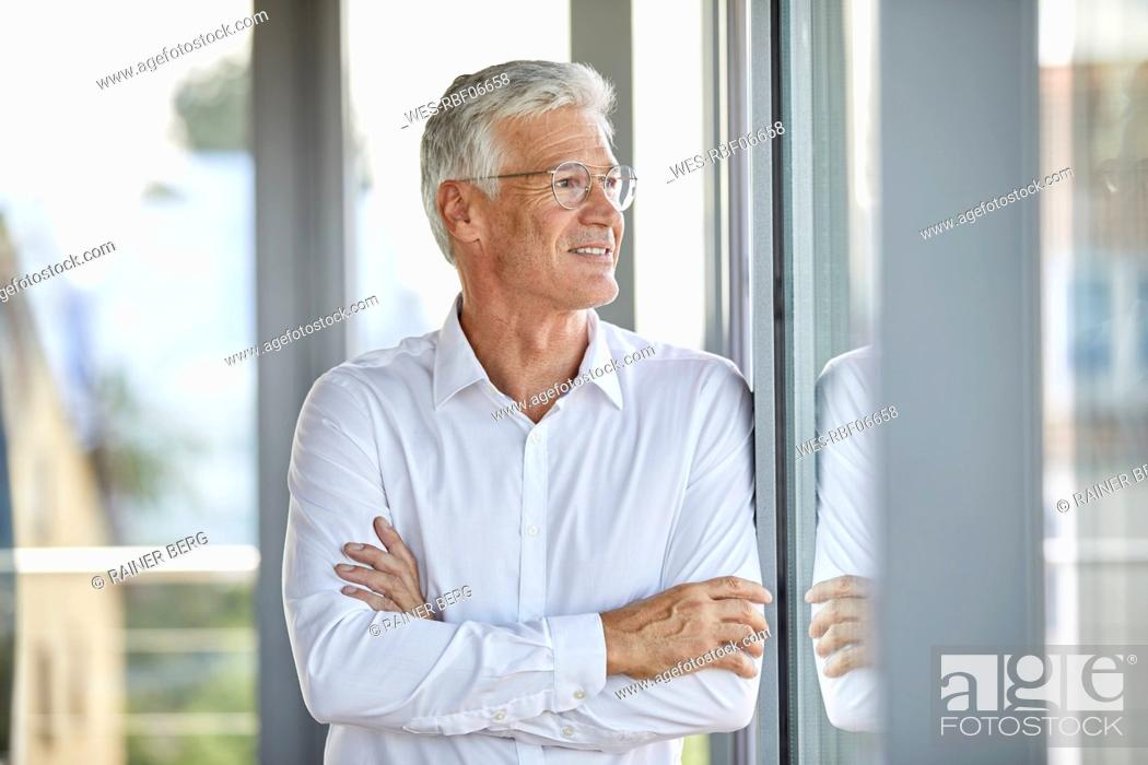 Stock Photo: Businessman in office leaning against window, with arms crossed.